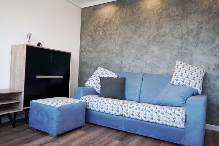 яркий светло-голубой диван с светлыми вставками рядом с серой стеной