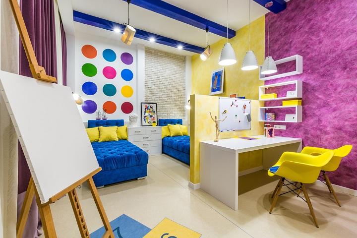 В этом интерьере детской комнаты множественное сочетание ярких и спокойных оттенков палитры. На противоположной стороны комнаты разместили шкафы и учебную зону.