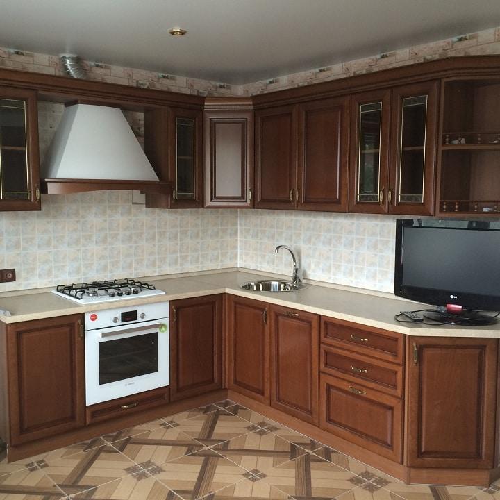 Угловая кухня из коричного дерева и бежевой отделкой.