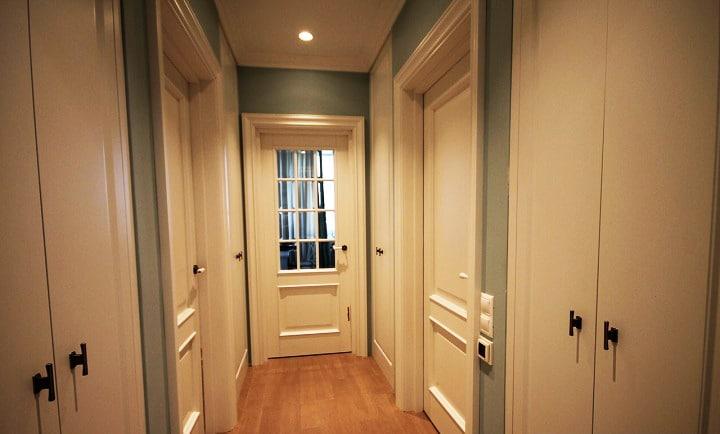 Коридор, обои под покраску, белые двери и два шкафа купе напротив друг друга.