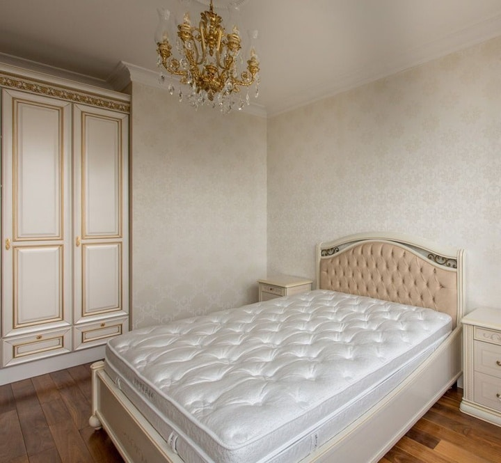 В этой спальной комнате решено ограничится только центральным освещением, люстра в золотом цвете. Обои бежевые с небольшим рисунком. На шкафу продублирована окантовка золотистого цвета.