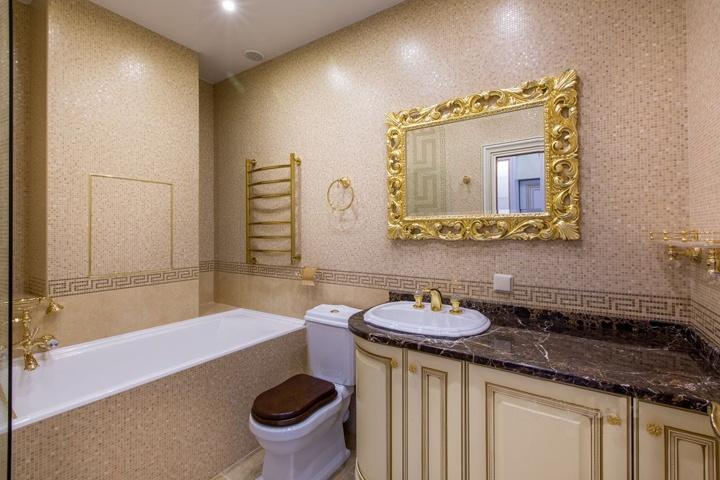 Мы стремились создать в каждой комнате и помещение однотипную концепцию, как в цветовом решение, так и по мебели. В ванной комнате уложена мозайка светло бежевого оттенка. Темная столешница подчеркивает роскошь и стиль в интерьере. А медная фурнитура вносит заключительные штрихи и завершает стиль.