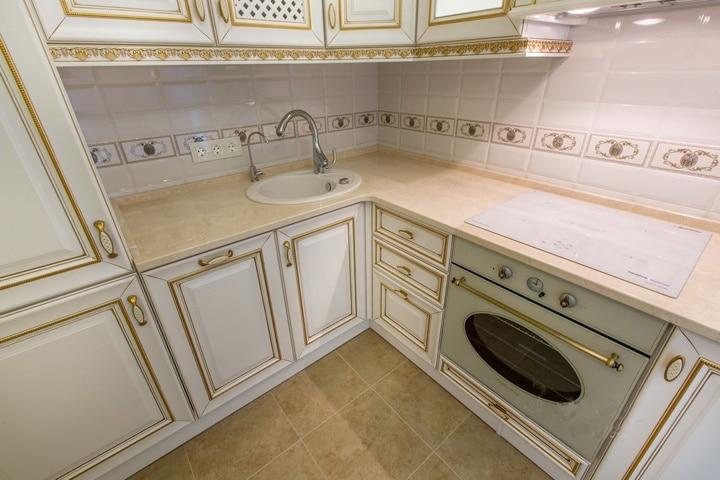 Переходим у кухонному гарнитуру. Типовая окантовка белого фасада с золотистыми линиями. Духовка и варочная панель в стиль интерьера. Фартук изготовлен из классической белой плитки с мелким рисунком.