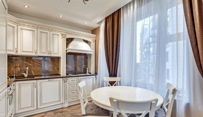 Белая классическая кухня, коричневая столешница под мрамор и фартук из того же материала. Дизайн проект в ЖК «Парк Апрель», планировка студии.