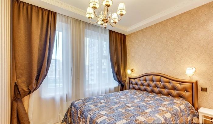 В спальне шторы спрятаны за карниз, богатый коричневый цвет шелка и кожи. Обои примерно того же оттенка без лишних декоров и вставок.