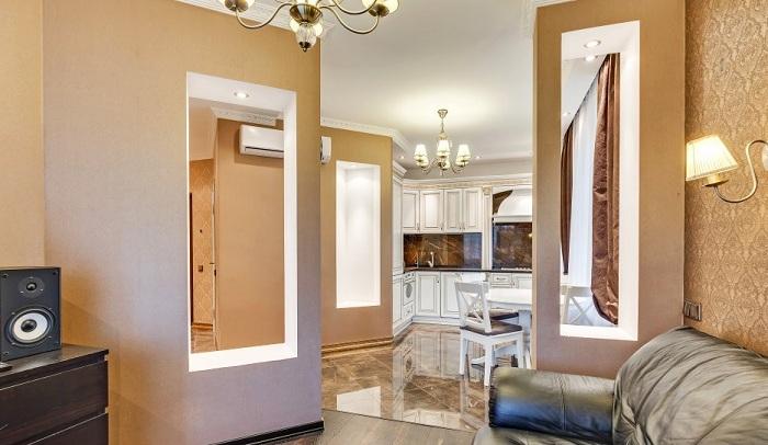 Прихожая и комната гостиная огорожена небольшими стенами с вставками из гисокартона. Внутри проведены точечные светильники для подсветки темных зон.
