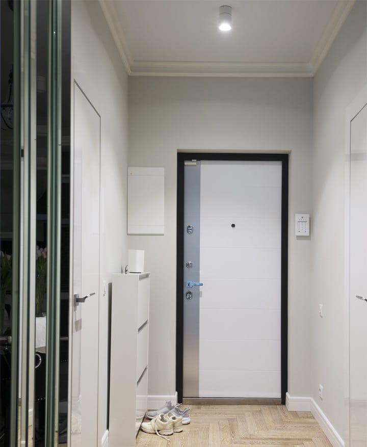 Двери в квартире выбраны плоские и не выступают, смотрится все единым целым. Щит электрический не стали прятать, домофон разместили на соседней стене.