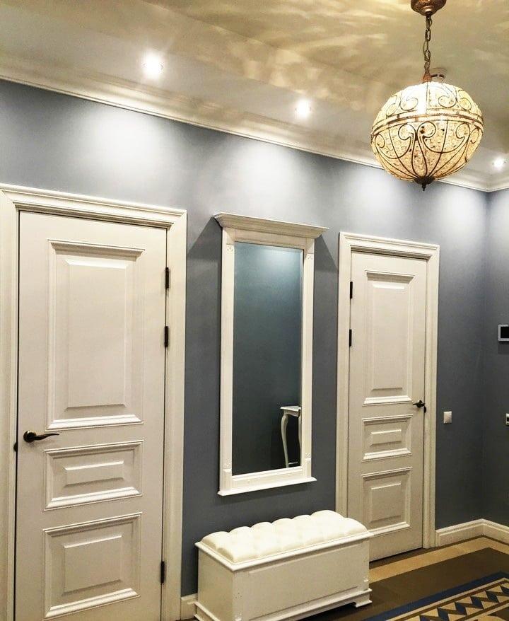 Прихожая изготовлена в одном стиле с квартирой, белый высокие двери, плинтуса в тот же цвет, темные обои под покраску и центральное украшение помещения - это зеркало с пуфиком. Дизайн проект ЖК Саларьево Парк, планировка.