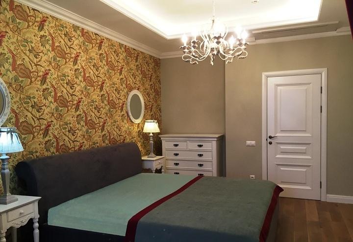 В спальне продолжается общий дизайн интерьера. Обои за спинкой кровати в не крупный цветочек, а по стенам однотонные обои под покраску с немного зеленовато сером цветом.