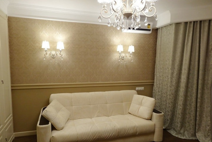 В помещении предусмотрен большой центральный свет, а так же два двойных ночных светильника по бокам от дивана. Мы предлагали сделать дополнительные выключатели по обе стороны дивана. Но заказчик оставил только с одной стороны. Шторы убраны в нишу.