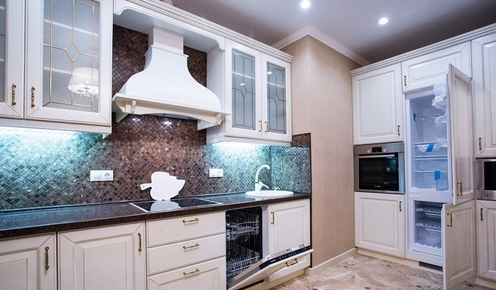 Подсветка верхних шкафов, фартук из мозаики повернутый на 45 градусов, встроенный холодильник. Дизайн проект квартиры в ЖК Солнцево, ул. Главмосстроя.