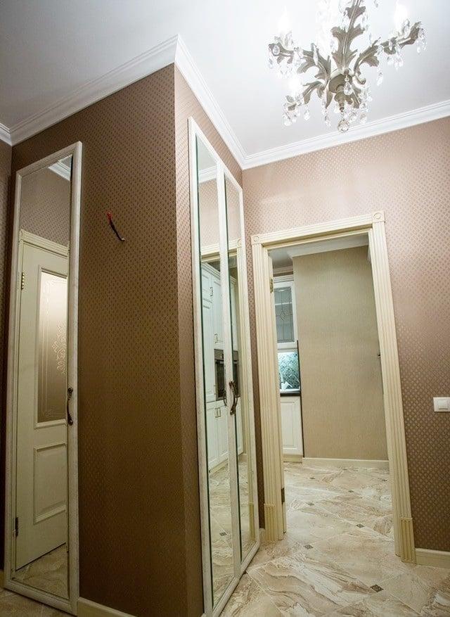В прихожей разместили встроенный шкаф зеркальный, откосы и двери так же в одном стиле с общим интерьером. Для увеличения высоты потолка мы увеличили размер бордюров, тем самым мы визуально подняли потолок.