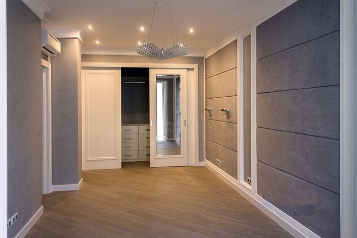 Большая спальня в серо белом оформлении в современном стиле. Особенность данной комнаты является встроенный гардероб с правильным оформление узлов примыкания. Двери выбраны с зеркальными элементами в белом классическом исполнении. Они подвешиваются с внутренней стороны и крепление не видно со стороны спальни.