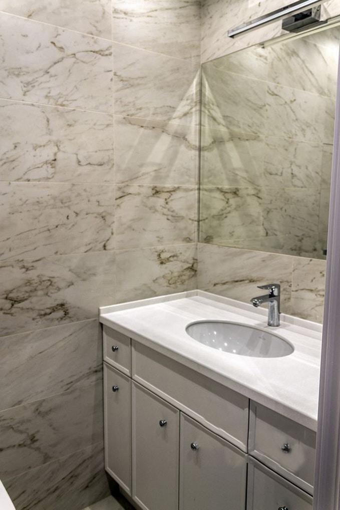 Фото зеркала с подсветкой и подвесной раковиной. Так как стиль в интерьере одинаковый, то и оформление в ванной комнате дублируется.