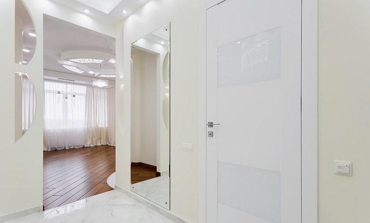 В прихожей смонтировано большое зеркало, плинтуса изготовлены из плитки. Под плиткой расположен теплый пол, справа от двери вы можете видеть регулятор теплого пола на уровне руку.