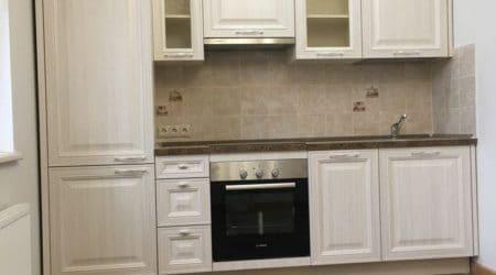 светлая кухня с встроенными и навесными шкафами белого цвета в сочетании с темным мраморным полом