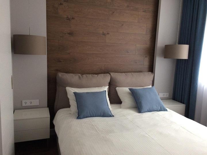 Стена спальни отделана ламинатом и положена светодиодная лента.
