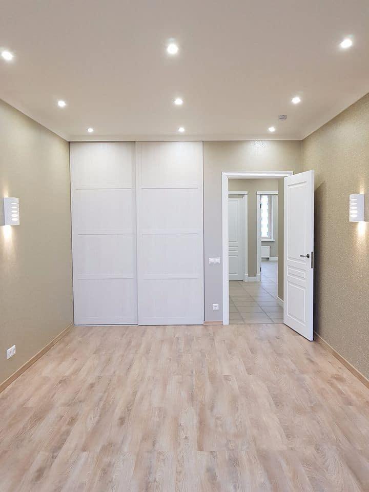 Одна из комнат в квартире, все оформлено в едином стиле и палитре красок. Светлый ламинат, натяжной белый матовый потолок. Центральное освещение не применяется, на смену ему установили больше одиночных ламп из светодиодов повышенной яркости. А так же бра над будущей кроватью в качестве вечернего освещения.