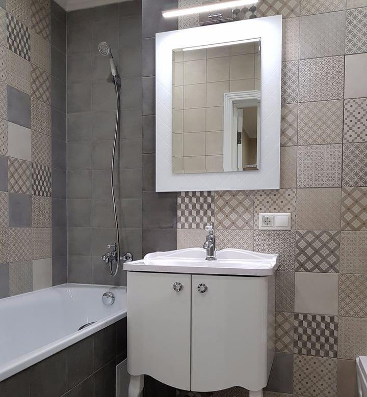 Теперь перейдем к ванной комнате и взглянем на простоту и в то же время стиль. Плитка серая с крупными вставками из мозайки. Так стены немного темные, то потребовалось дополнительное освещение зеркала. Плюс рядом с выключателем традиционная розетка для мелочей.