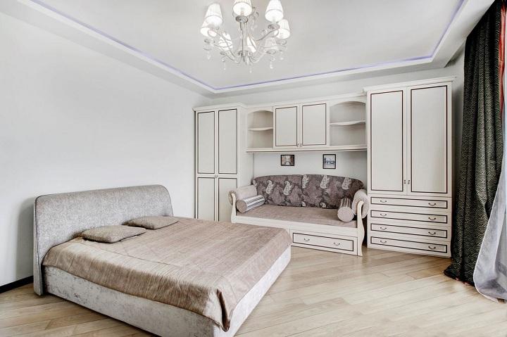Стиль - современная классика в спальне. Светлые тона с обрамлением из меди или золота. Диван разместился между двумя шкафами. При чем мебель вся стандартная и покупалась в сетевых магазинах.