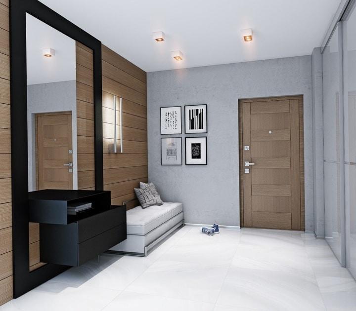 Минимализм в оформлении коридора. Серые и темные тона смешаны с белым напольным покрытием. Мебель квадратной формы сочетаются с квадратными светильниками на потолке.