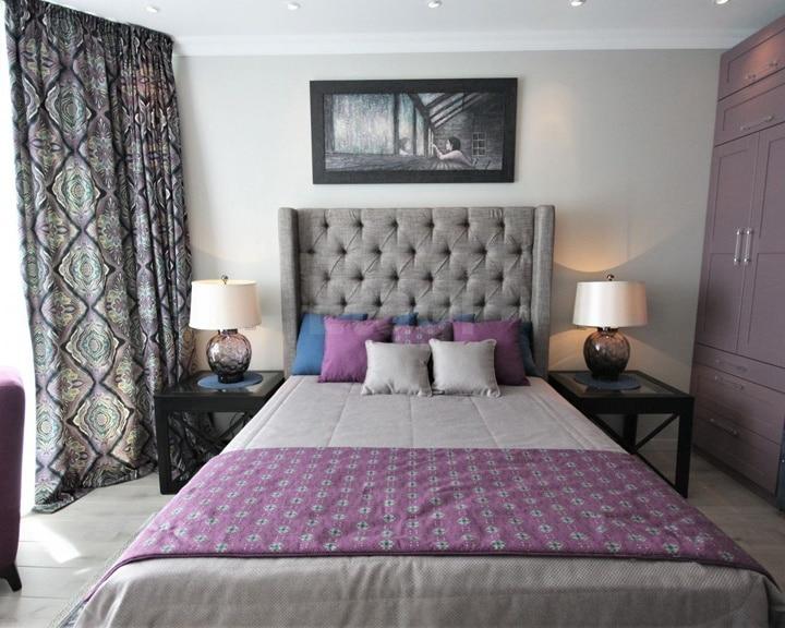 двухспальная кровать в сером цвете с двумя прикроватными столиками и настольными лампами на них