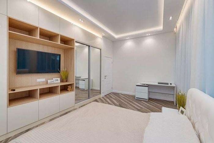 Белый матовый гарнитур, шкаф с светлыми вкраплениями дерева, смотрится волшебно. Большая двухспальная кровать с тумбами.