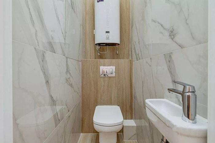 Современный туалет с отделкой белым мрамором и плиткой под ламинат.