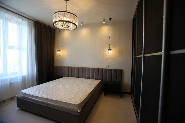 большое окно освещает двухспальную кровать в комнате с приглушенным светом