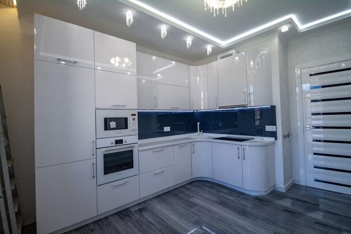 вид на белую укомплектованную кухню с встроенной универсальной печкой и ярко освещенной подсветкой