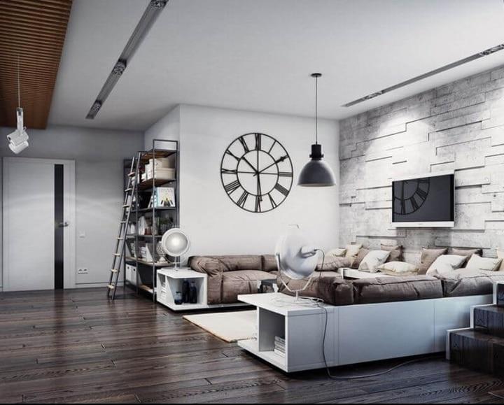 большая комната с мягким диваном кофейного цвета в сочетании с темным паркетом и белыми стенами