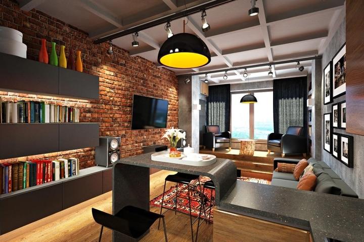 На потолке смонтированы балки деревянные и окрашены в один серый цвет. С двух сторон разместились световые короба, в них спрятаны кабеля, и освещает все помещение направленные источники света. Стена в красном кирпиче с телевизионной зоной и книжным шкафом, а напротив голая бетонная стена с комфортным диваном.