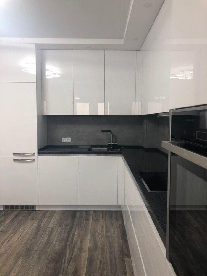 угловая кухня с белыми шкафчиками и сочетанием темной столешницы и краном