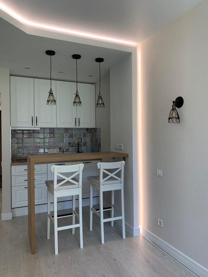 яркая подсветка маленькой светлой кухни с деревянным столом и высокими стульями