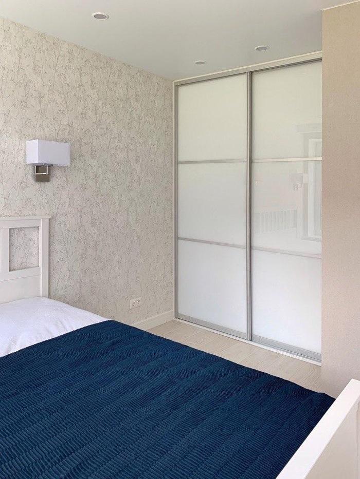Современная спальня со встроенным белым шкафом.