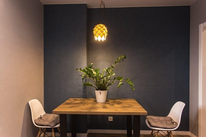 обеденный стол на черных ножках с двумя белыми стульями, освещается интерьер креативной лампой