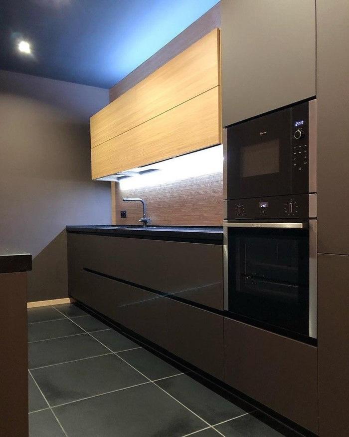 стильная кухня с мраморной столешницей и встроенной универсальной печкой в темно-коричневых цветах