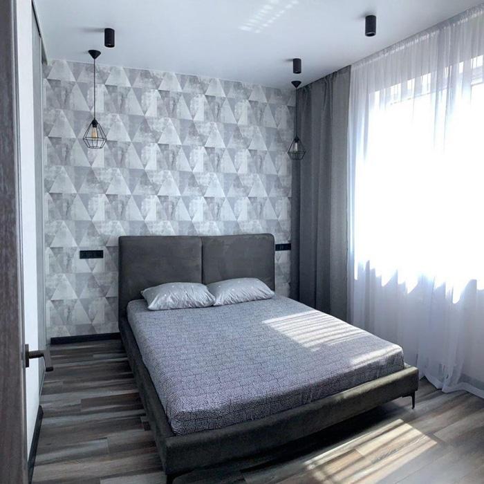 светлая спальня сделанная в серых оттенках, большая двухспальная кровать с маленькими подушками