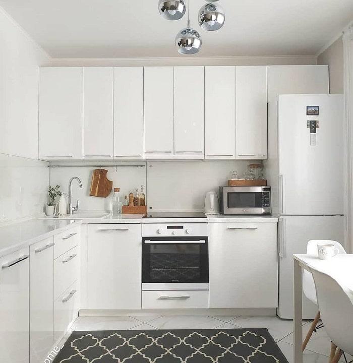 большая просторная кухня в белом тоне с контрастным узорчатым ковров