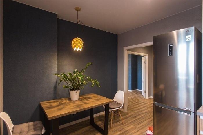Вид из кухня на прихожую, просторный коридор. Люстра свисает точно над столом.