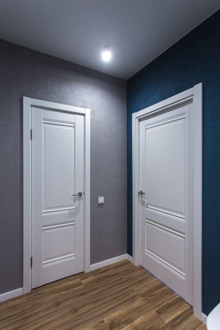 Белые двери и темные стены в прихожей.