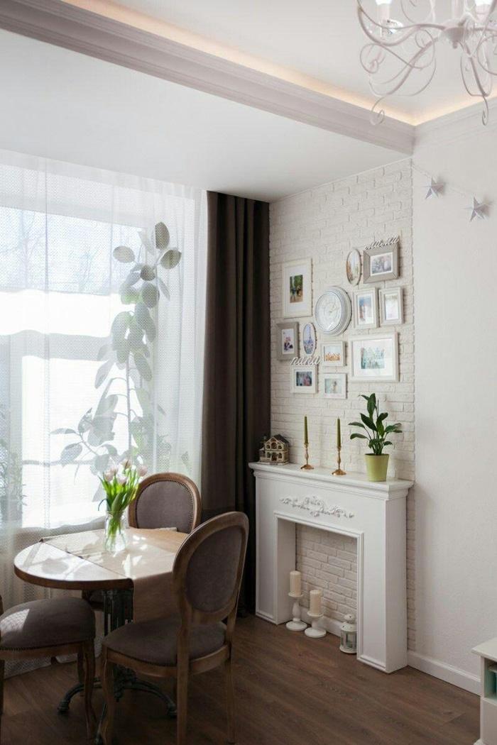 круглый стол с мягкими стульями возле большого светлого окна