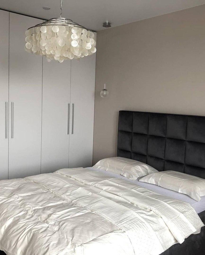 Серые стены в спальне с белой дверью и мебелью.
