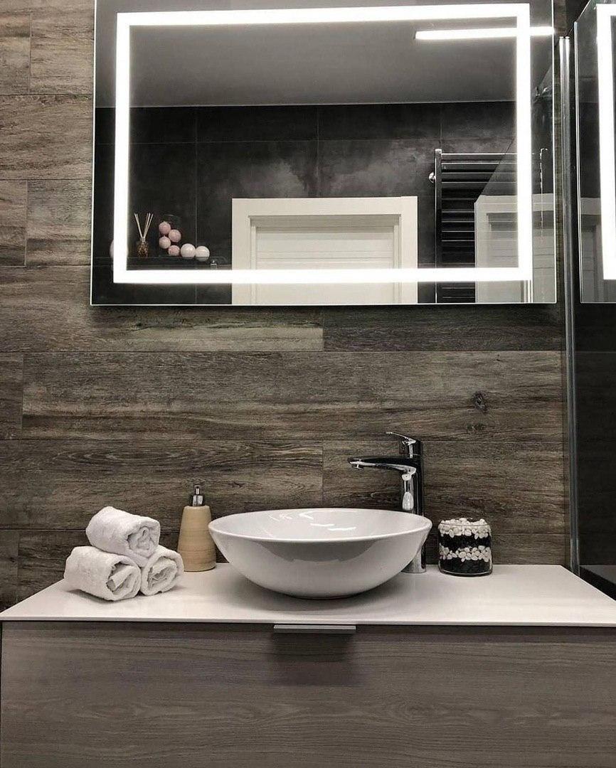 Квадратное зеркало с подсветкой, стены ванной отделаны керамогранитом под ламинат.
