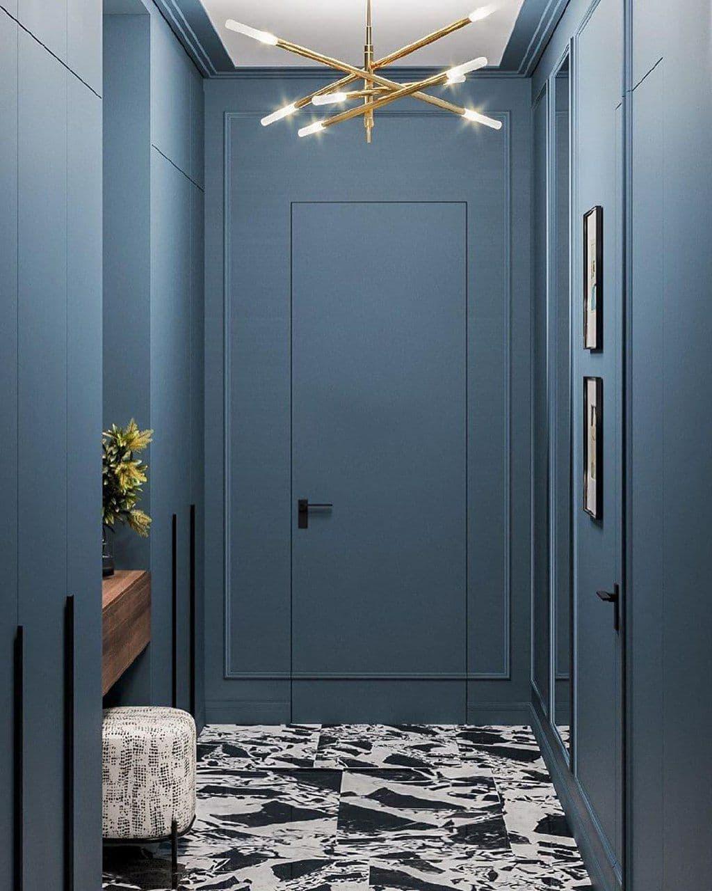 Скрытая дверь в интерьере под покраску. Тонкая подвесная люстра. Необычное напольное покрытие с хаотичным рисунком.
