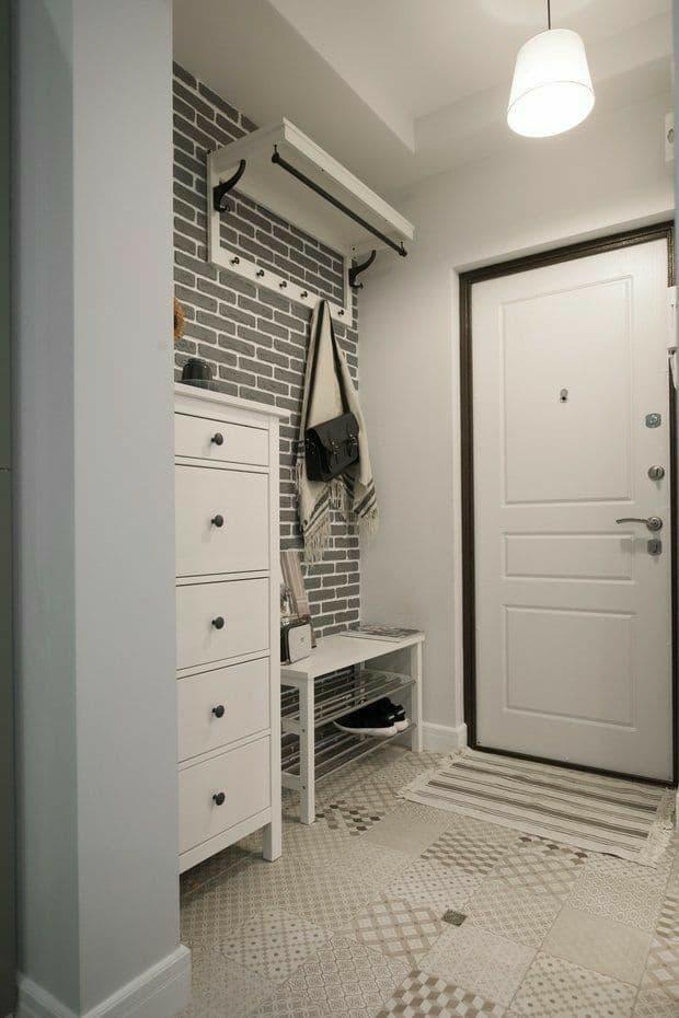 Белая входная зона в квартиру с отделкой кирпичом. Мебель классическая с черными ручками. Входная дверь резная с окантовкой.